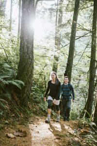 A fit older adult couple in their 50's hike through a sunlit forest trail in the Columbia river gorge, autumn leaves visible on the ground. They smile as they make their way through the woods. Vertical image with copy space. A depiction of discovery and adventure while enjoying nature, fresh air, and exercise.